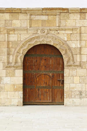 Medieval wooden door with arch entrance in courtyard Stock Photo - 17249595