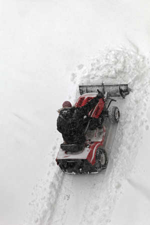 Small tractor with plow removing heavy snow photo