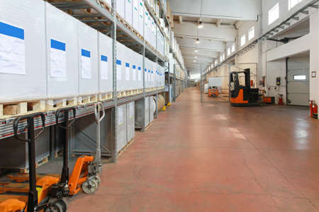 Distribution warehouse with shelves and forklifts in long corridor photo