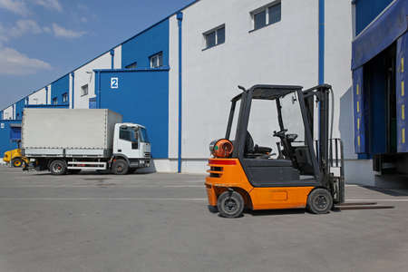 Forklift and truck in front of distribution warehouse photo