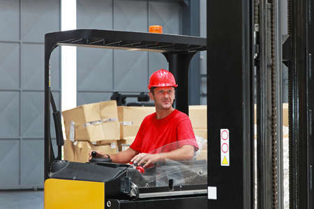Forklift driver with red helmet  in distribution warehouse photo