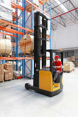 Forklift loading pallet with roll in distribution warehouse photo