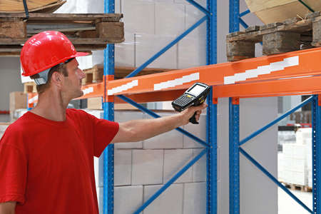 Worker in distribution warehouse with handheld barcode scanner