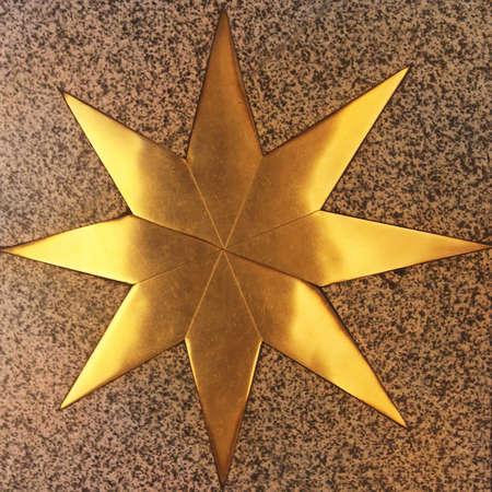 octagonal: Estrella de oro octogonal en m�rmol en la iglesia Foto de archivo