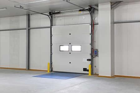 garage doors: Closed automated cargo door in distribution warehouse Stock Photo
