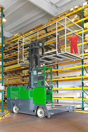 Side loaded forklift with basket in wood warehouse photo