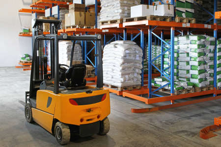Yellow forklift in distribution warehouse with sacks photo