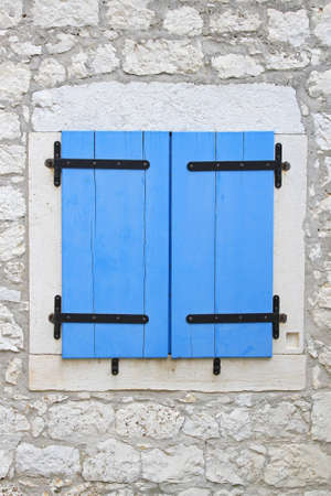 Closed blue window blinds at stone house Stock Photo - 18397934