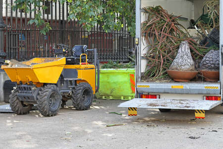 skip: Skip Loading Dumper and truck loaded with plants Stock Photo