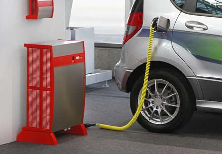 Electric vehicle with plugged cable in charging station Archivio Fotografico