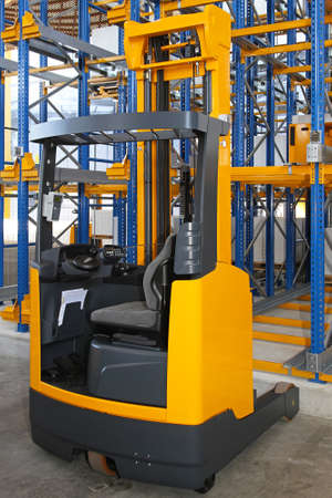 Yellow high rack stacker forklift in warehouse photo