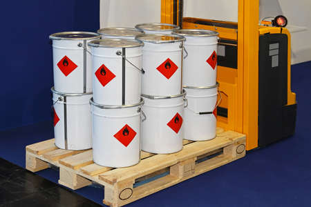 material: Industrial bucket cans with flammable material at forklift pallet