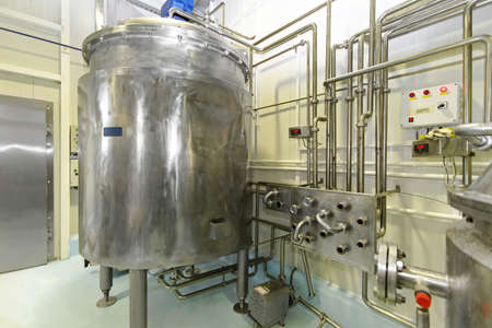 Dairy factory with milk pasteurization tank and pipes photo
