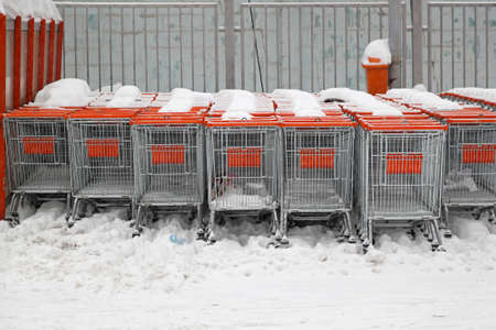 Shopping carts under the snow at supermarket parking lot photo