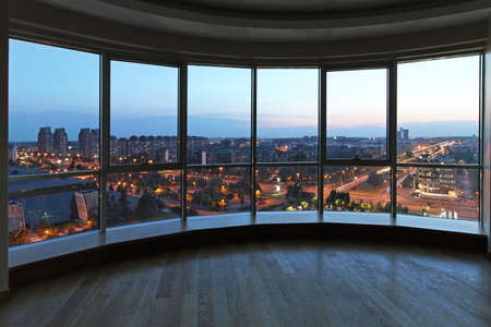 penthouse: Big glass wall in oval living room with cityscape view Stock Photo