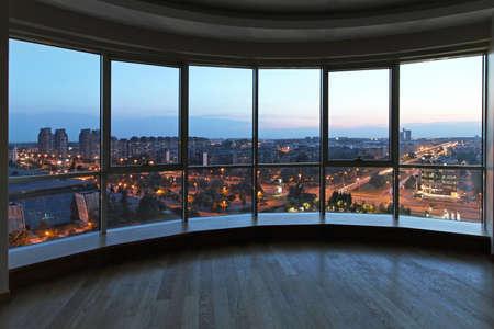Gran pared de cristal en el salón oval con vista de la ciudad