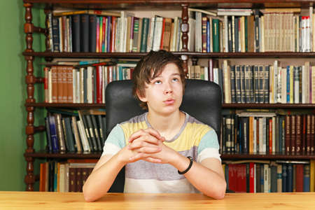 Teenage boy boring in library look up photo