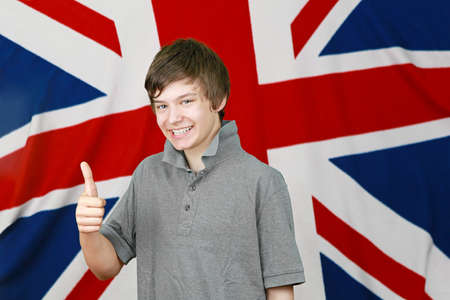 Young British boy thumbs up in front of Union Jack flag photo