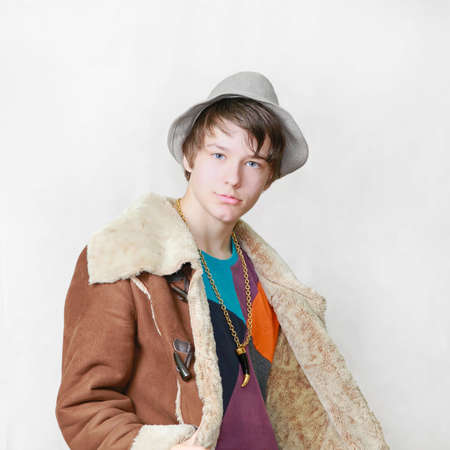 Teenage boy in gang style with coat and hat photo