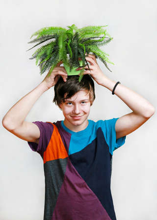 Teenage boy goofing around with plant at head Stock Photo - 19270515