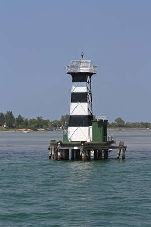navigational light: Black and white lighthouse in harbor channel