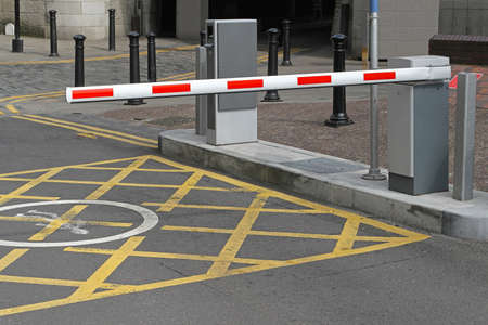 security barrier: Rising arm access barrier at car park Stock Photo