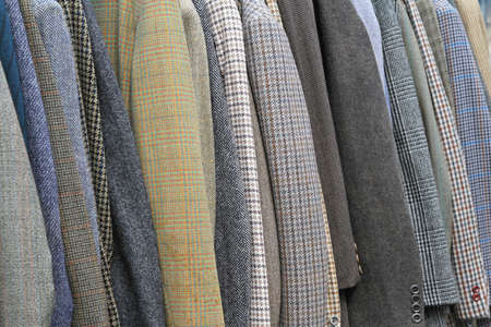 coat hangers: Vintage style suits and coats at rail Stock Photo