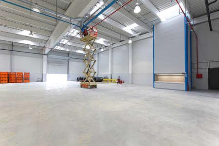 New distribution warehouse hall with hydraulic scissors lift platform Archivio Fotografico