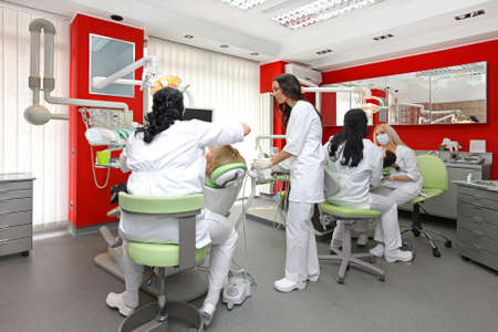 Dentists at work in modern red dental office Stock Photo