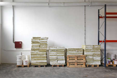 Pallets with construction material in storage room