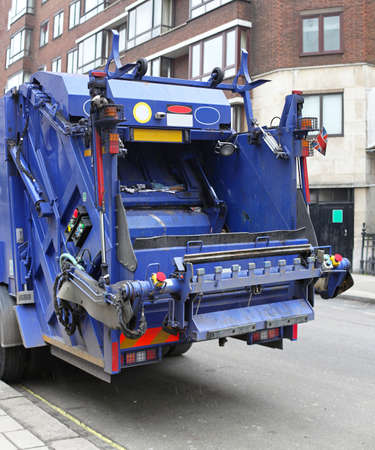 Back of a big blue garbage truck in city