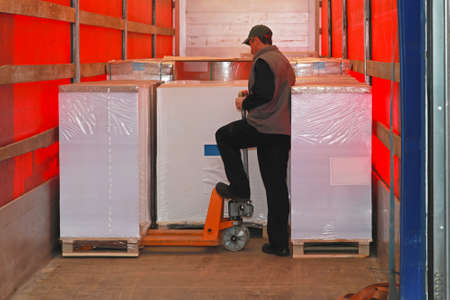 Loading goods in lorry truck with pallet jack Standard-Bild