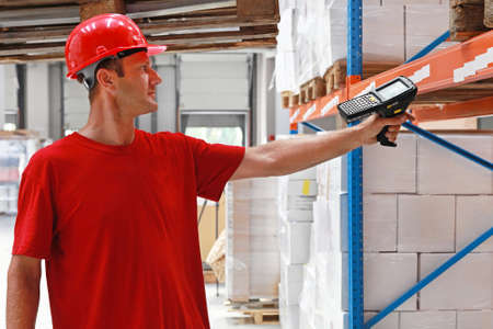 barcode scanner: Worker in distribution warehouse with handheld barcode scanner