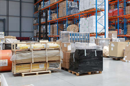 Distribution warehouse with big bunch of goods at floor photo