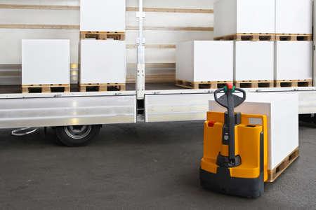 Heftruck laden pallets met papier in de truck Stockfoto