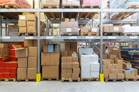 Boxes with goods at shelves in warehouse