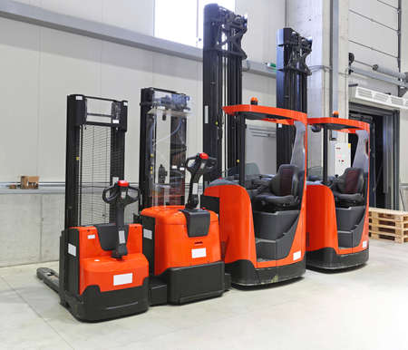 Four red forklift trucks in distribution warehouse Archivio Fotografico