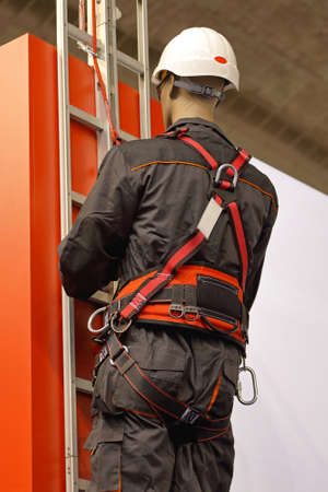 Worker on a ladder uses a safety harness to prevent falling from the building