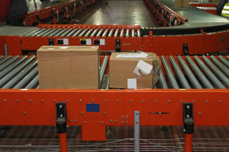 Shipping boxes at conveyer belt in distribution warehouse