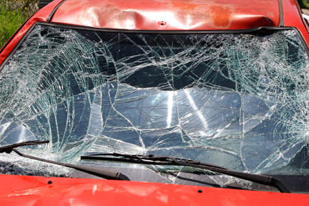 Broken Windshield at Red Car in Traffic Accident Stock Photo