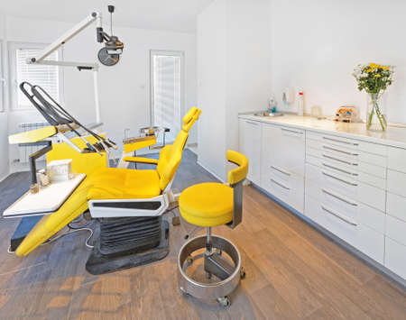 치과 의사 사무실에 노란색 치과 의자와 의자