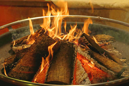 Log Fire in Circular Metal Firepit Tray Stock Photo