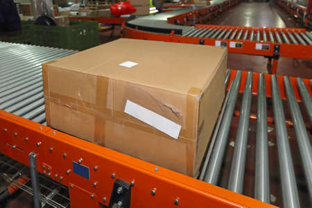 Shipping Box at Conveyor Belt in Distribution Warehouse