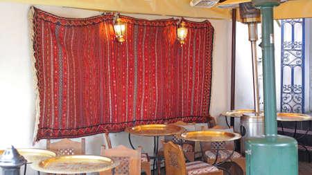 Marokkanisches Art-Café mit Messingtabellen und Teppich an der Wand Standard-Bild - 83937675