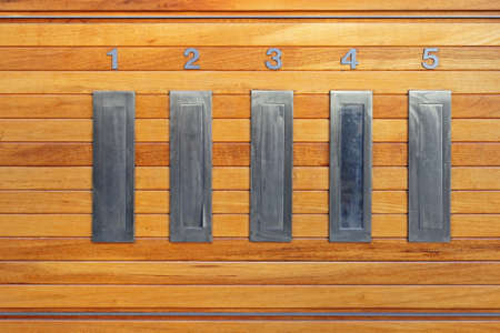 Letterbox Slots in Building Interior at Wooden Wall Stock Photo