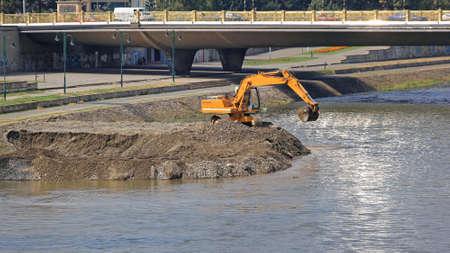 Excavator Machine Digging Levee at River Embankment