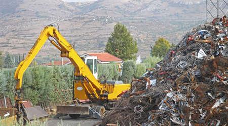 Stapel van schroot en graver op recycling faciliteit Stockfoto