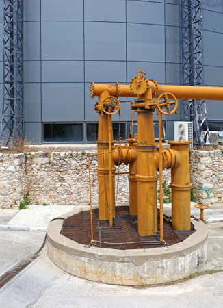 Big Industrial Pipes with Valves in front of Big Tank
