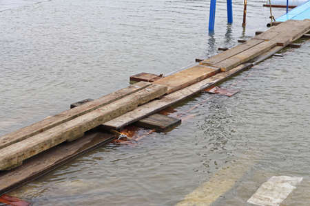 Floating Plank Boards Bridge Over Flood Water Stock Photo