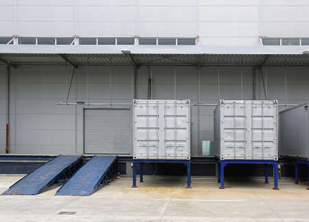 Silver Shipping Containers and Ramp in Front of Warehouse Фото со стока